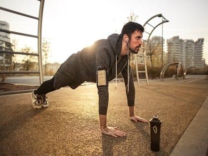 man-in-gray-jacket-doing-push-ups-during-sunrise